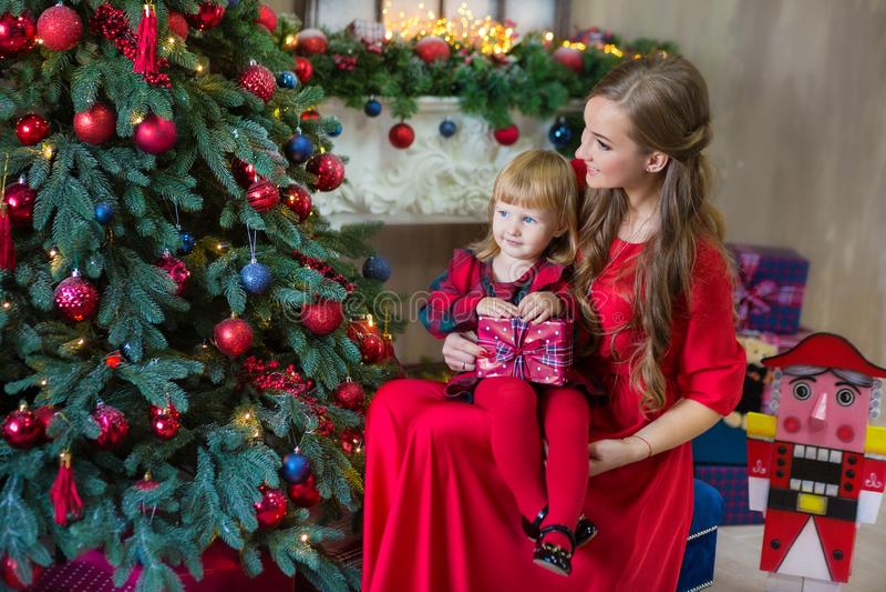 圣诞快乐和节日快乐妈妈和女儿在屋子里装饰树 户内爱恋的家庭 免版税图库摄影