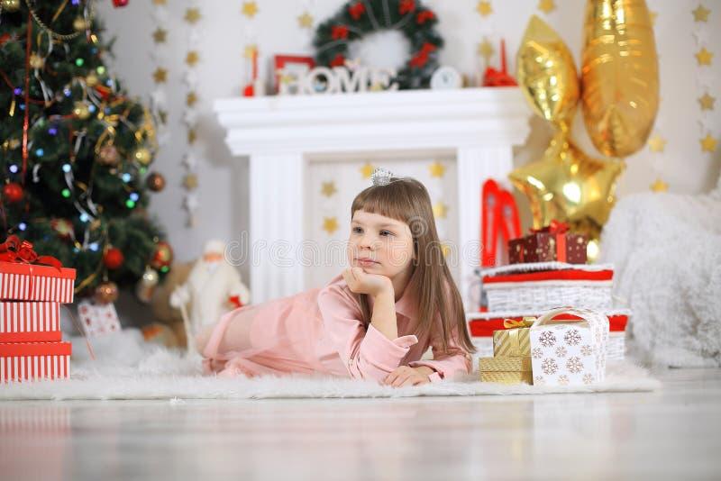 圣诞快乐和节日快乐逗人喜爱的小孩女孩装饰圣诞树户内 图库摄影