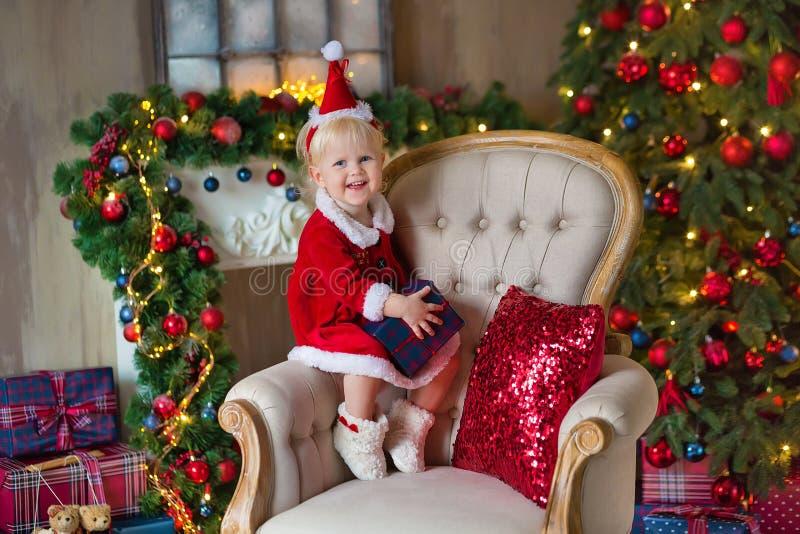 圣诞快乐和节日快乐逗人喜爱的小孩女孩装饰圣诞树户内 免版税库存照片