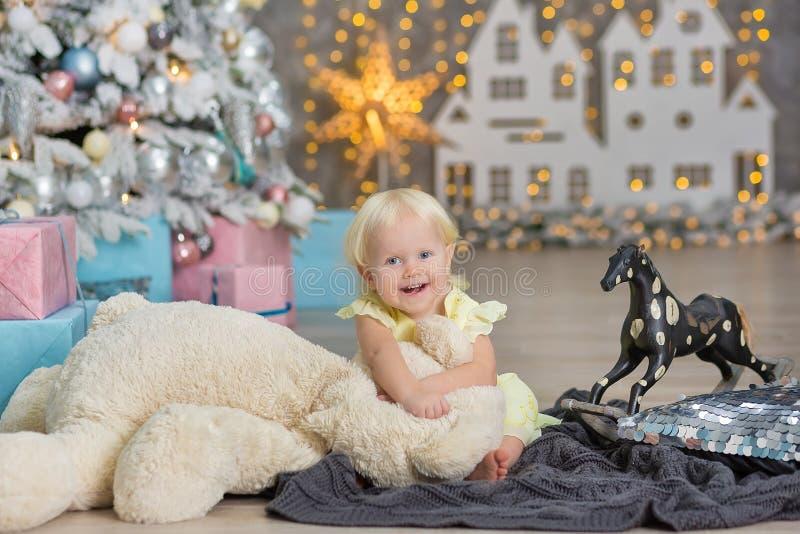 圣诞快乐和节日快乐逗人喜爱的小孩女孩装饰圣诞树户内 免版税库存图片