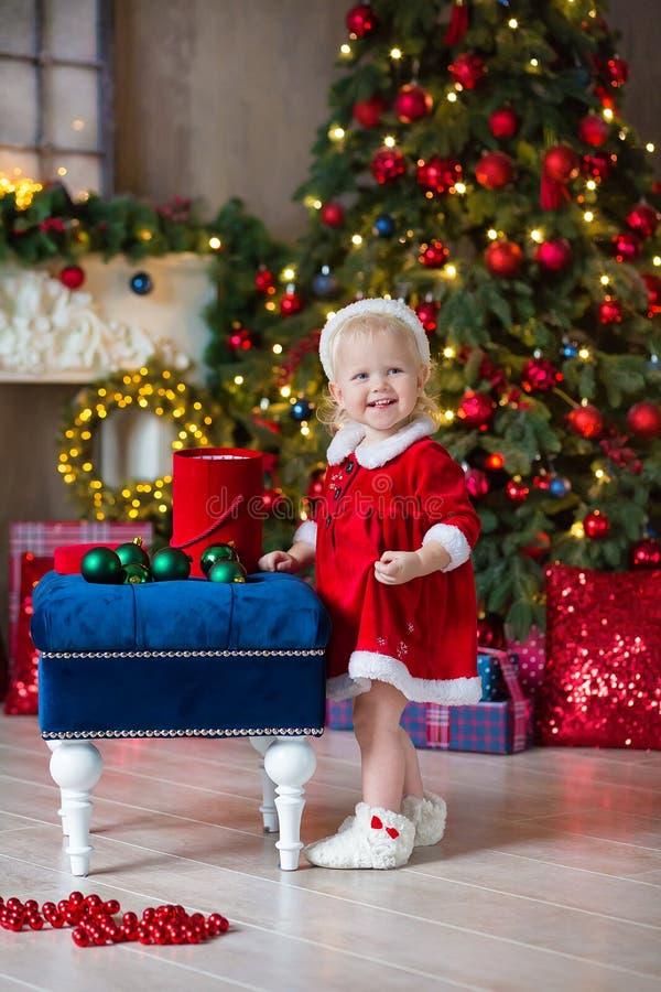 圣诞快乐和节日快乐逗人喜爱的小孩女孩装饰圣诞树户内 免版税图库摄影