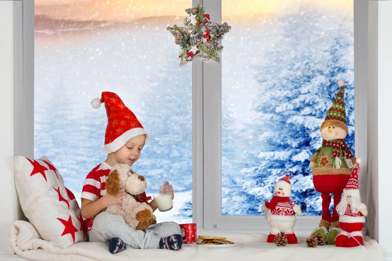 圣诞快乐和节日快乐!一个小男孩坐并且使用与玩具狗哺养牛奶和曲奇饼 库存照片
