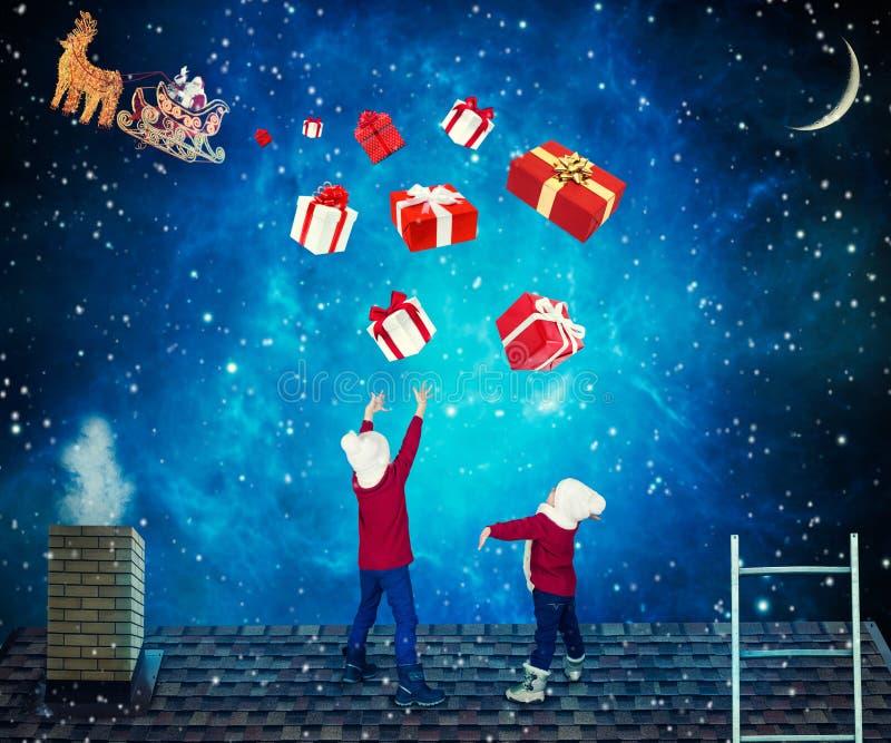 圣诞快乐和节日快乐!孩子捉住有礼物的箱子从圣诞老人 圣诞老人投下了礼物对ro的小孩子 免版税库存照片