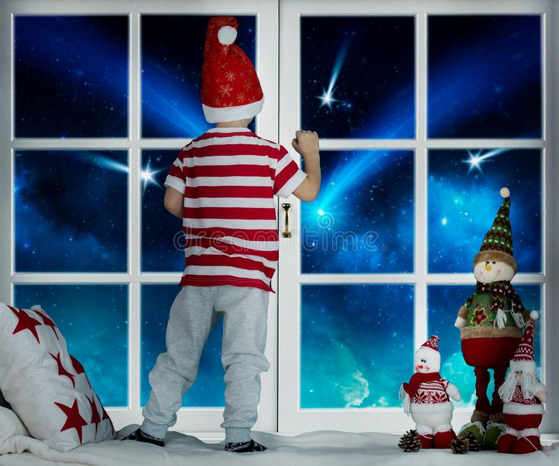 圣诞快乐和节日快乐!小孩男孩在窗口和看starfall站立 在圣诞节装饰的室 孩子e 库存图片