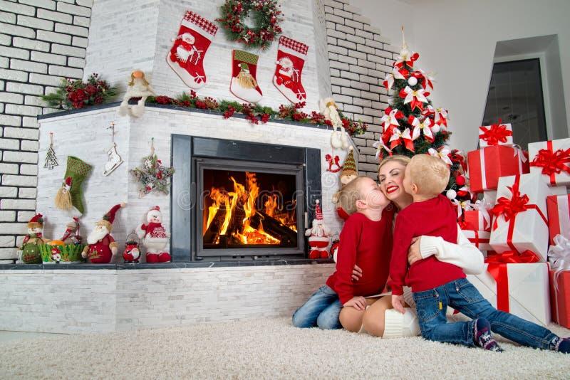 圣诞快乐和节日快乐! 两个小儿子亲吻妈妈 家庭休息在圣诞树下由壁炉 库存照片