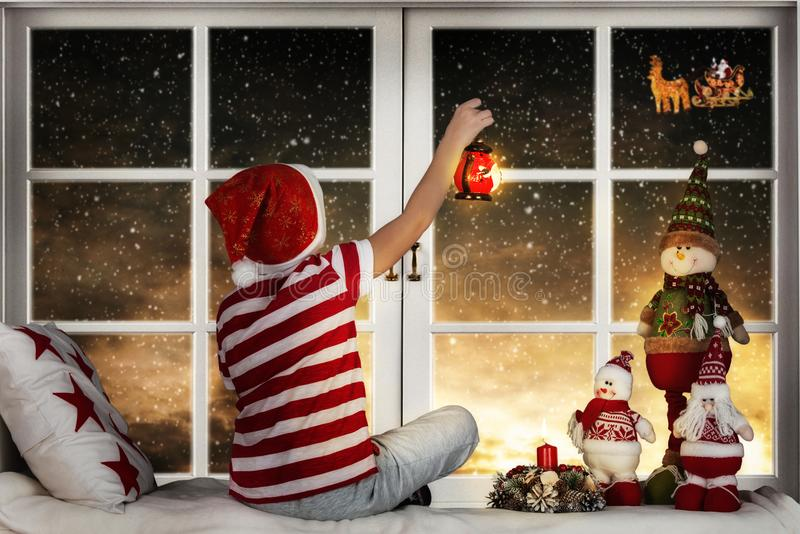 圣诞快乐和节日快乐!坐窗口和看在他的雪橇的小男孩圣诞老人飞行反对月亮 免版税图库摄影