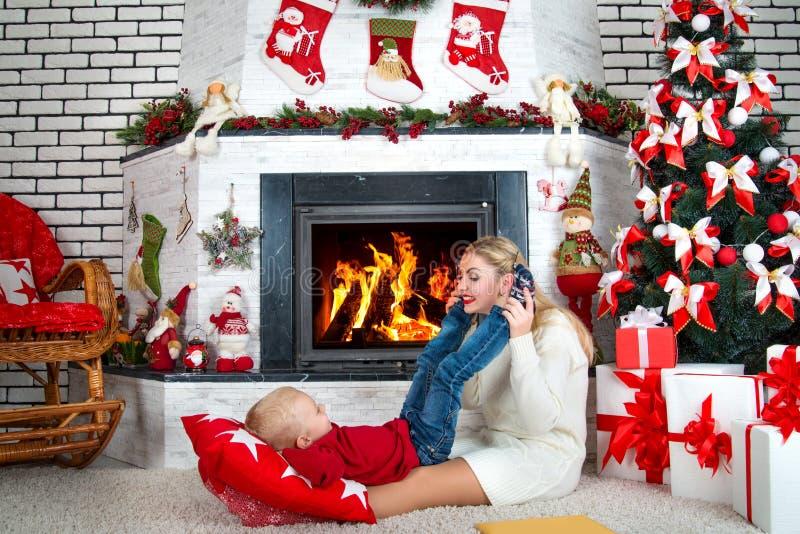 圣诞快乐和节日快乐! 妈妈和小儿子在晚上在壁炉附近,家庭晚上休息 库存照片