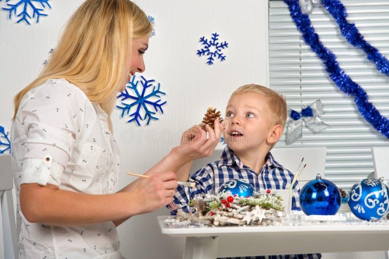 圣诞快乐和节日快乐! 母亲和儿子装饰与闪烁的杉木锥体 家庭创造圣诞节int的装饰 库存照片