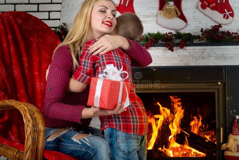 圣诞快乐和节日快乐! 逗人喜爱的儿子给他心爱的母亲一件礼物 新年` s内部在客厅 免版税库存图片