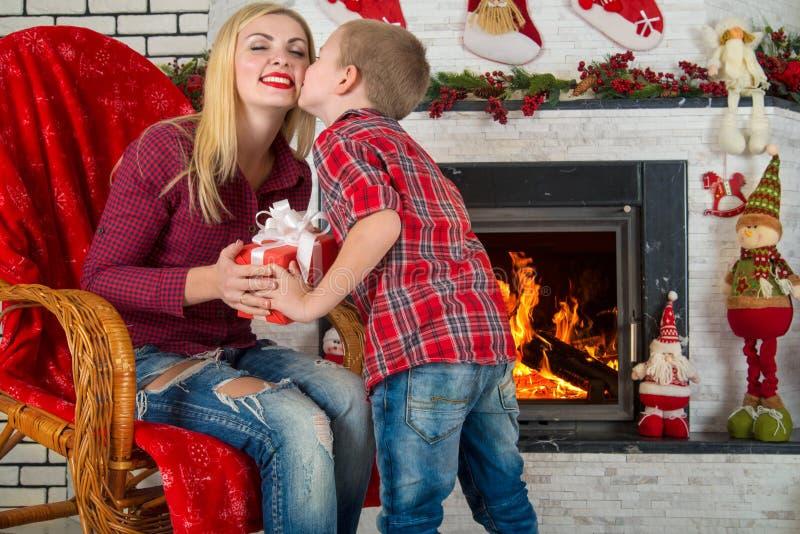 圣诞快乐和节日快乐! 逗人喜爱的儿子给他心爱的母亲一件礼物 新年` s内部在客厅 库存照片