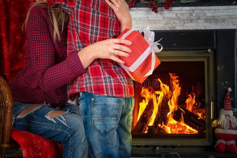 圣诞快乐和节日快乐! 逗人喜爱的儿子给他心爱的母亲一件礼物 新年` s内部在有壁炉的客厅 库存图片