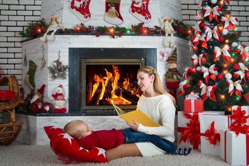 圣诞快乐! 妈妈读一本书给有童话的一个小儿子 家庭在壁炉附近休息 免版税图库摄影