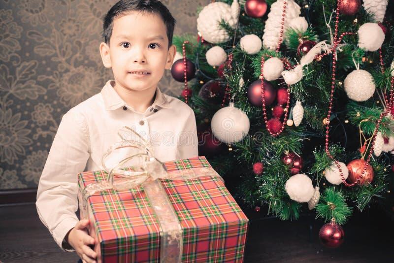 圣诞快乐!拿着礼物盒的愉快的男孩 免版税库存图片