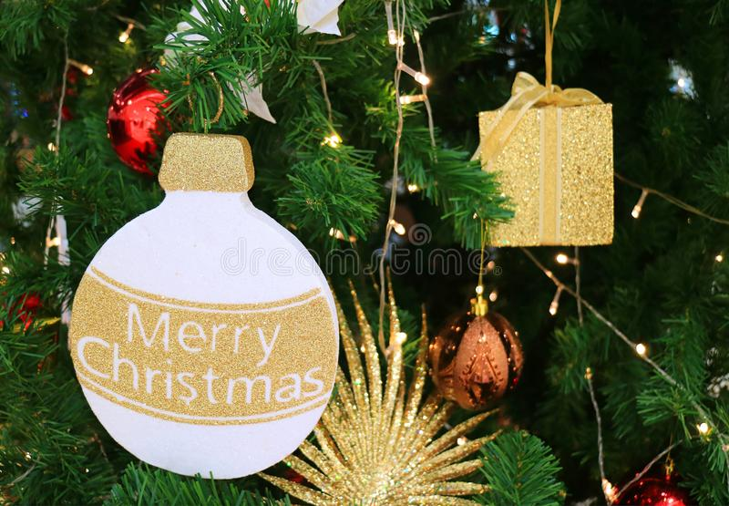 圣诞快乐!!许多金黄垂悬在一棵闪耀的圣诞树的闪烁和发光的装饰品 库存照片