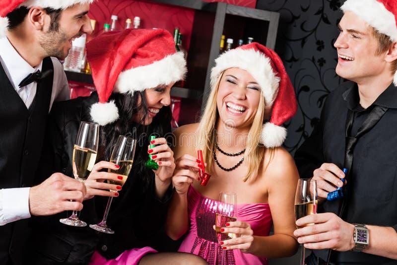 圣诞晚会朋友获得乐趣在棒 库存照片