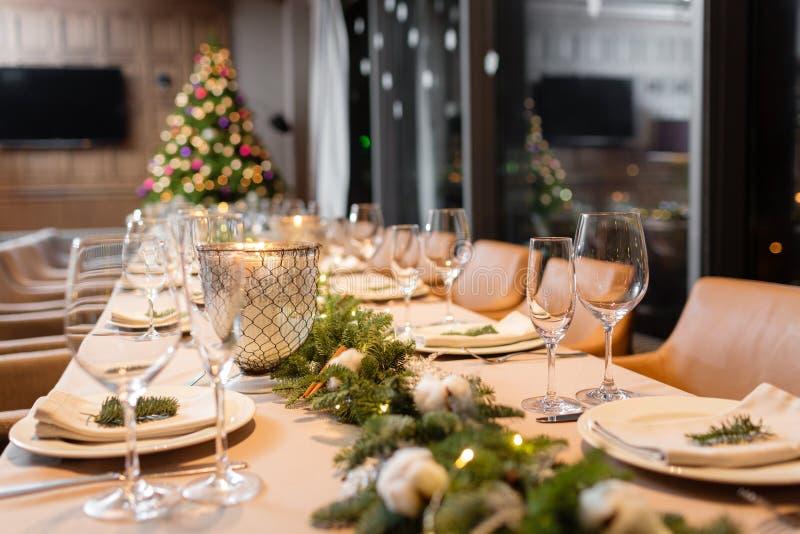 圣诞晚餐宴餐A在背景中装饰了与香槟玻璃的餐桌和圣诞树 免版税图库摄影
