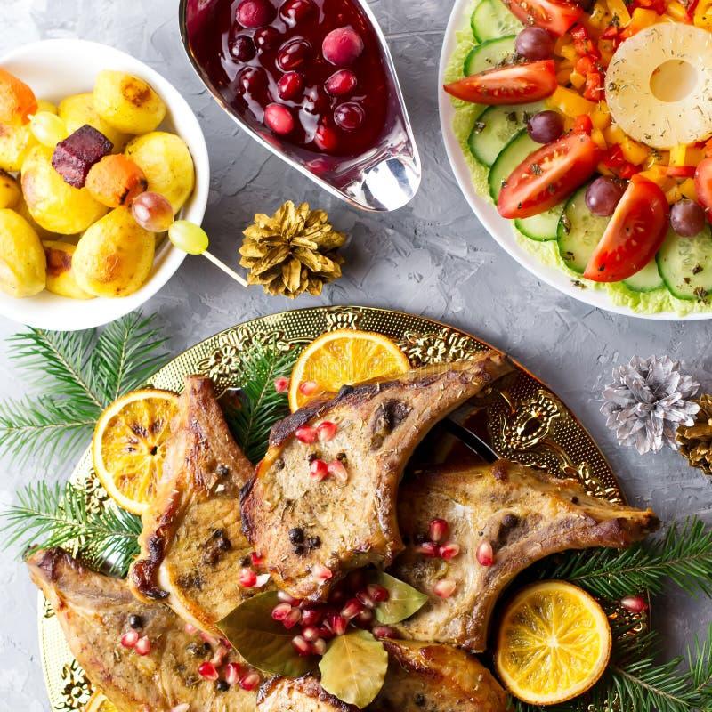 圣诞晚餐用烤肉牛排,圣诞节花圈沙拉,被烘烤的土豆,烤菜,酸果蔓酱 库存照片