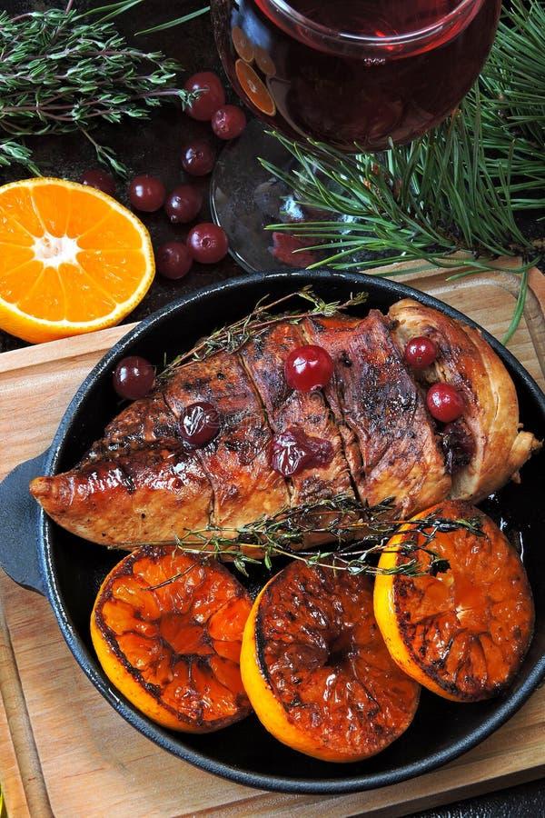 圣诞晚餐 鸡胸脯烘烤用蜜桔和蔓越桔 圣诞树分支和一杯酒 圣诞节moo 免版税图库摄影