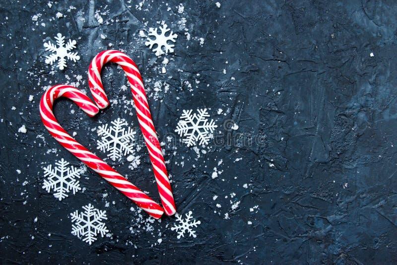 圣诞曲 深蓝色背景中雪的糖果 冬季,新年概念 平躺、顶视图、复制空间 免版税库存照片