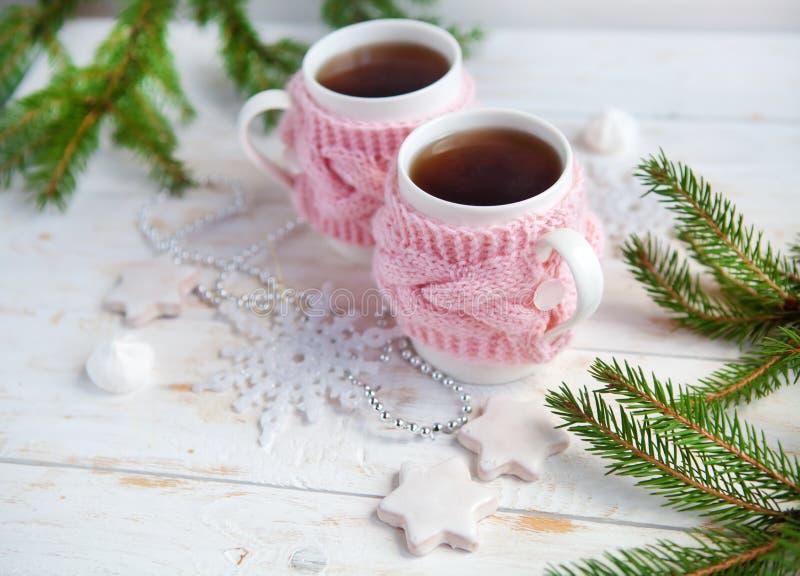 圣诞树、曲奇饼和杯子在被编织的杯座的热的茶在白色木桌上 库存照片