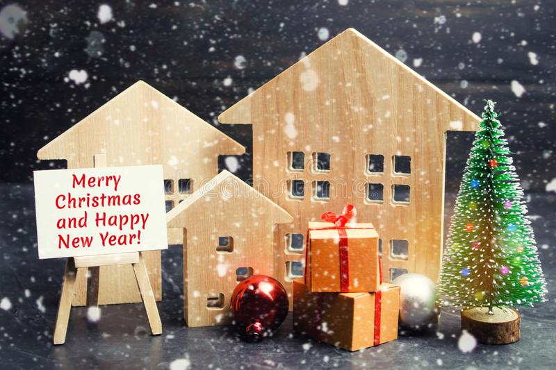 圣诞树、木房子和礼物与题字 免版税库存图片