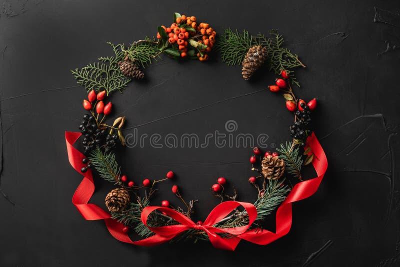 圣诞树分支、杉木锥体、莓果和红色松驰冠,在黑石背景 免版税库存图片