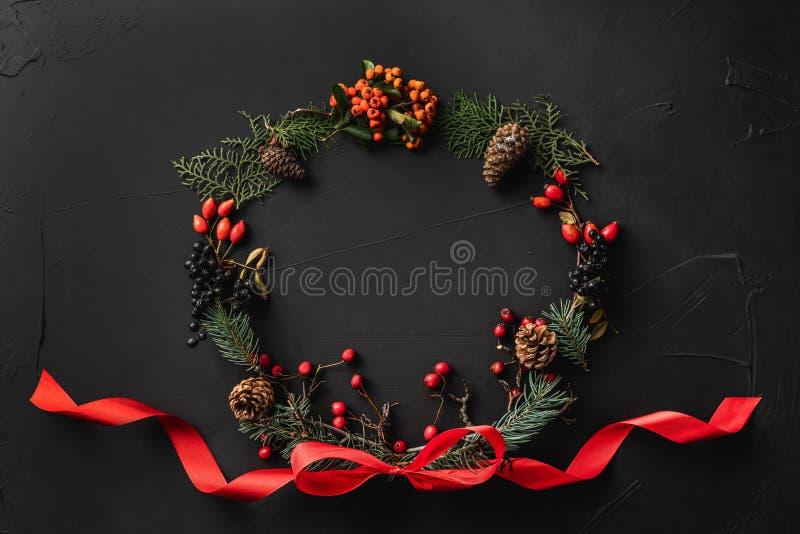 圣诞树分支、杉木锥体、莓果和红色松驰冠,在黑石背景 免版税图库摄影
