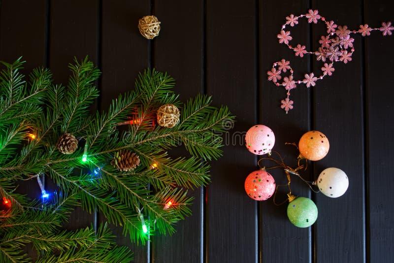 圣诞树分支、雪花、锥体、五颜六色的光和球在黑暗的木背景 免版税库存照片