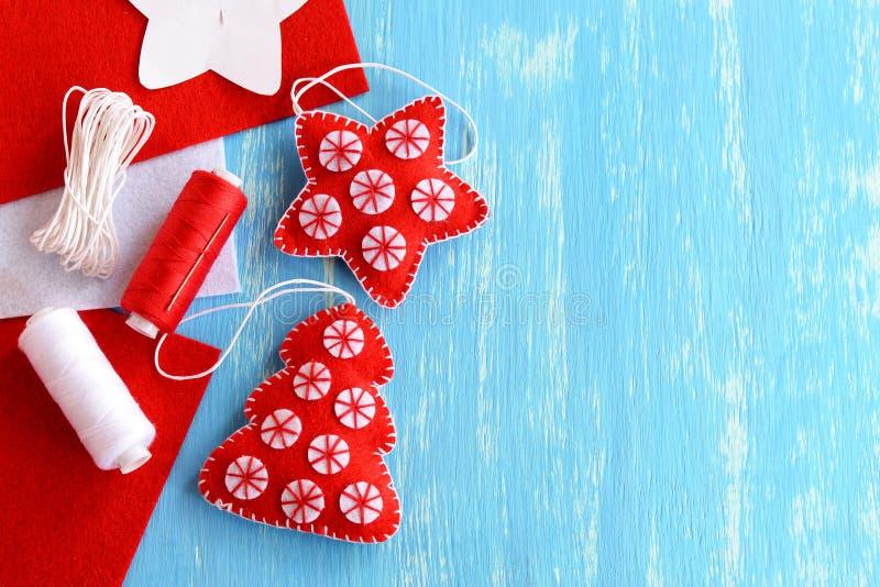 圣诞树和星由毛毡制成在与空白的蓝色木背景文本的 手工制造圣诞节玩具 库存照片