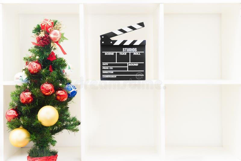 圣诞树和电影拍板在空的白色书架 库存图片