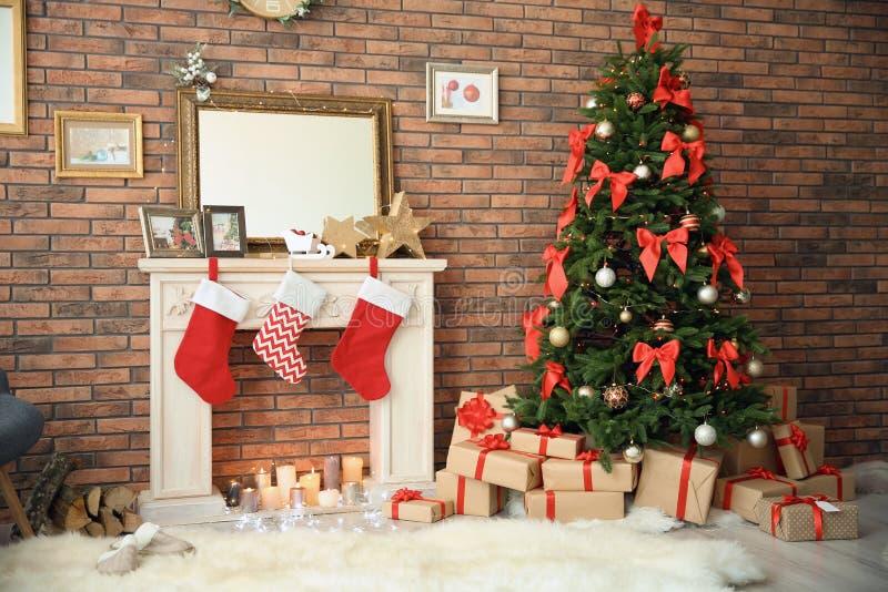 圣诞树和礼物临近与长袜的装饰壁炉户内 免版税库存图片