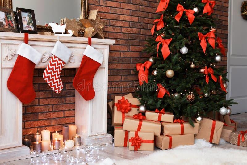 圣诞树和礼物临近与长袜的装饰壁炉户内 库存照片