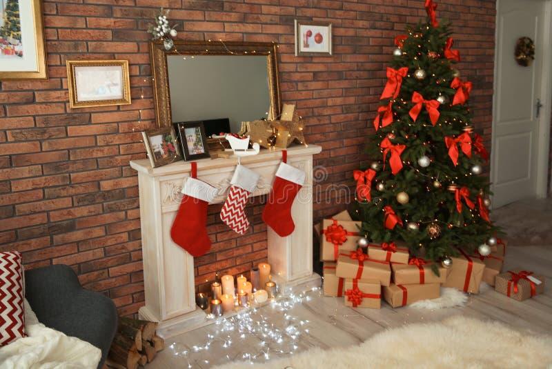 圣诞树和礼物临近与长袜的装饰壁炉户内 库存图片