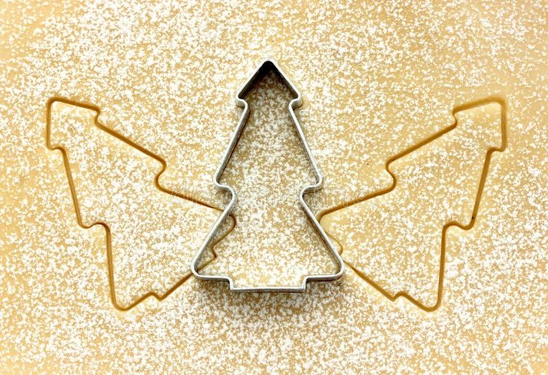 圣诞树在未加工的面团的曲奇饼切削刀 prepar圣诞节的食物 免版税库存照片