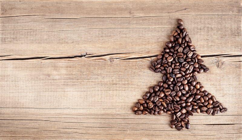 圣诞树形状由咖啡豆制成在木桌 免版税库存图片