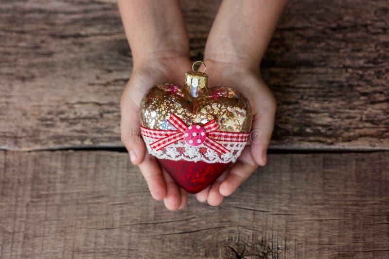 圣诞树玩具心脏在孩子的手上 新年度 圣诞节 木背景 免版税图库摄影