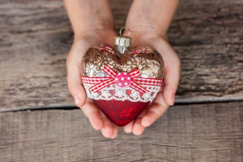 圣诞树玩具心脏在孩子的手上 新年度 圣诞节 木背景 免版税库存照片