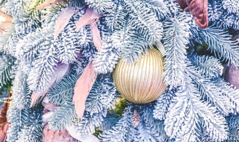 圣诞树玩具装饰和积雪的圣诞树分支 免版税库存照片