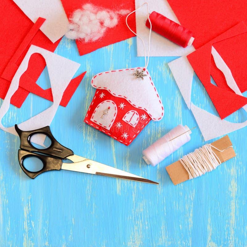 圣诞树用雪花和金属元素缝合从红色和白色毛毡和装饰的房子装饰 工具和材料 图库摄影