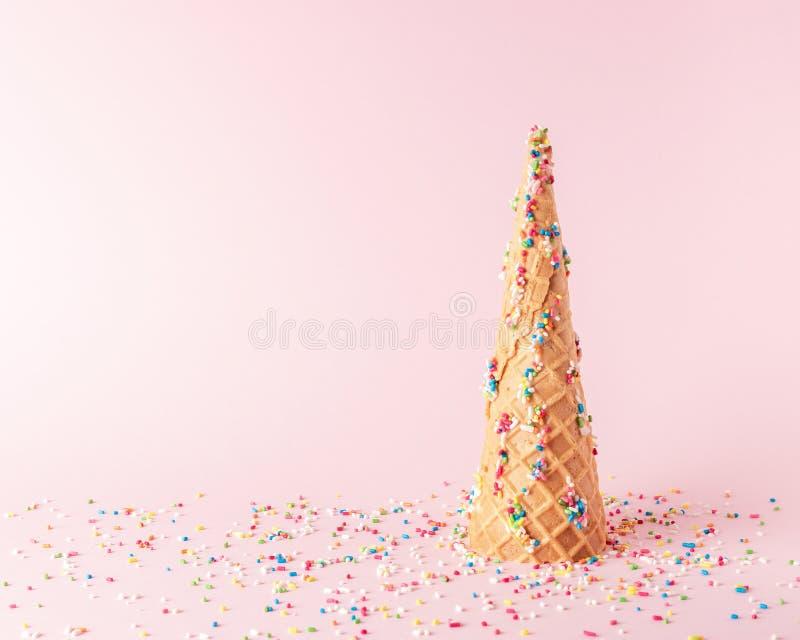 圣诞树由与甜颜色装饰的冰淇淋锥体制成在桃红色背景 圣诞节或新年最小的概念 库存照片