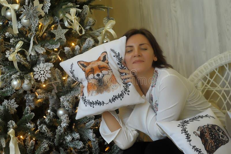 圣诞树的愉快的妇女 免版税库存图片