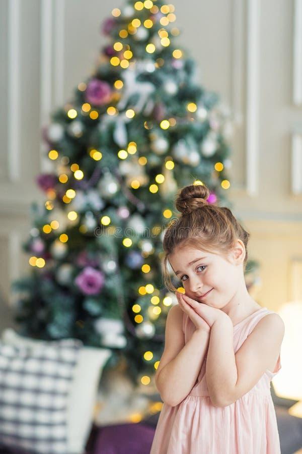 圣诞树的背景的逗人喜爱的女孩 一个孩子的画象新年内部的 免版税库存照片