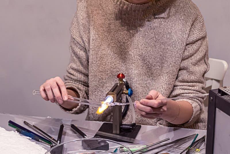 圣诞树的装饰员吹玻璃器玻璃管基地的工作戏弄舒展的热化扭转在煤气喷燃器m的基地 免版税库存图片