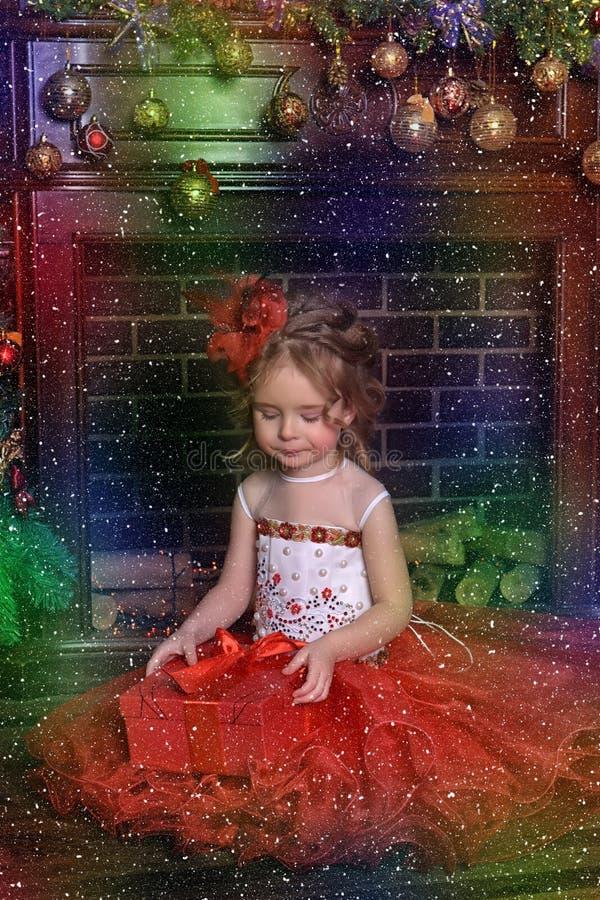 圣诞树的逗人喜爱的女孩在红色舞会服装 免版税库存图片