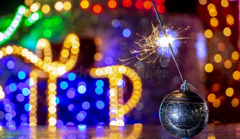 圣诞树装饰和燃烧的闪烁发光物关闭bakcground 库存照片