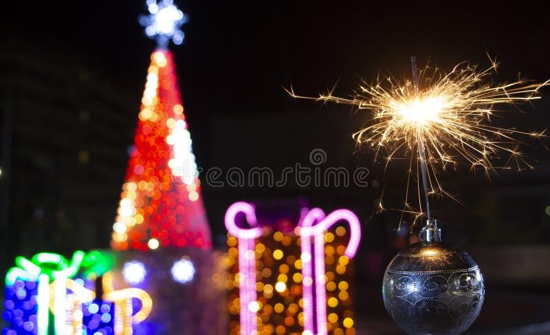 圣诞树装饰和燃烧的闪烁发光物关闭bakcground 库存图片