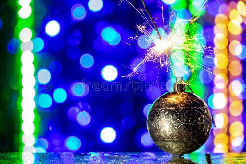 圣诞树装饰和燃烧的闪烁发光物关闭bakcground 免版税库存图片
