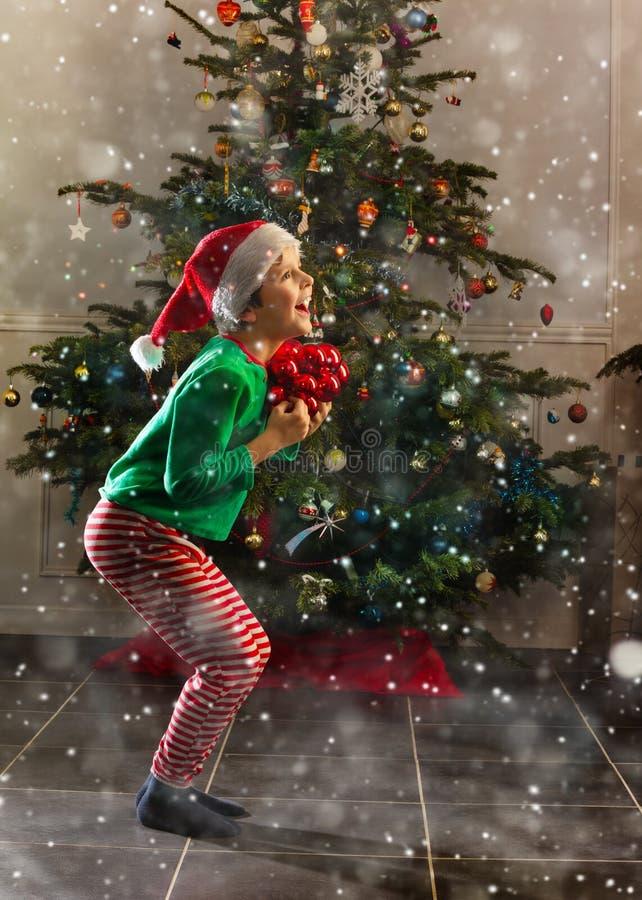 圣诞树附近快乐的男孩 免版税库存照片