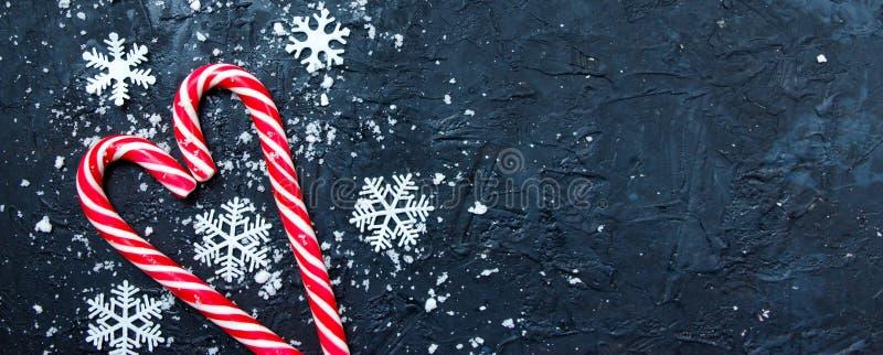 圣诞横幅组合 深蓝色背景中雪的糖果 冬季,新年概念 平躺、顶视图、复制空间 免版税库存照片
