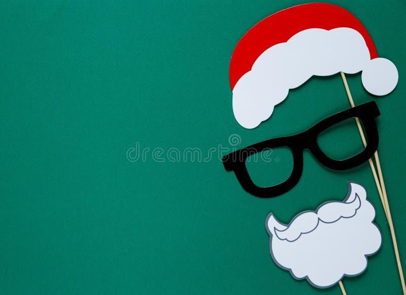 圣诞派对的-圣诞老人帽子,玻璃,在绿色背景的胡子照片摊五颜六色的支柱 库存图片